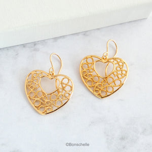 18K gold plated filigree heart earrings with 14K gold filled earwires shown on a surface