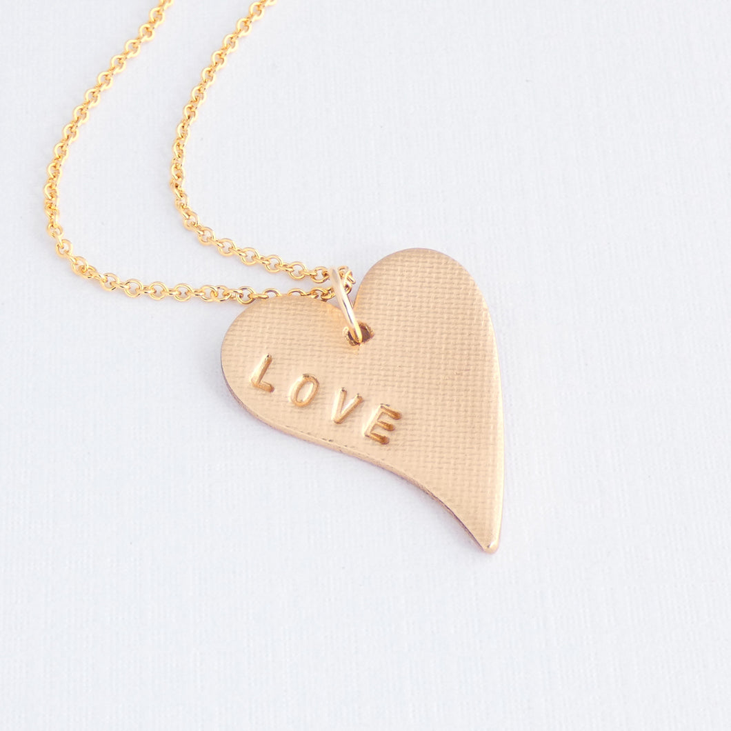 handstamped bronze love heart necklace with the word 'love'