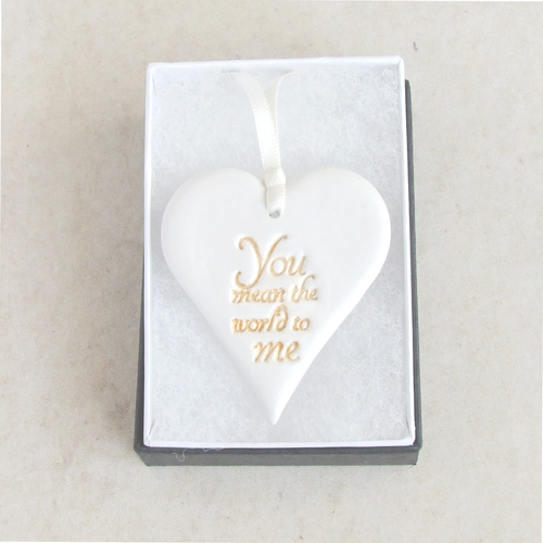 Heart shaped hanging ornament made from white clay with gold words 'You mean the world to me' , laying in a gift box.