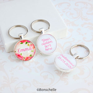 Double sided silver toned round keyring with a name and floral design on the front and your custom text on the back showing an additonal example of text on the back.