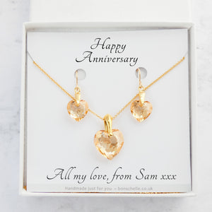 handmade necklace and earrings jewellery set for women made with pale gold colour crystal cut Swarovski heart beads, 14K gold filled chain and 14K gold filled earwires shwon in a jewellery box with a personalised gift message