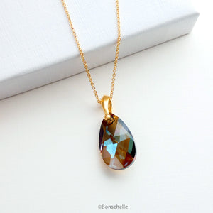 Handmade necklace with a teardrop shape bronze toned Swarovski cut glass crystal bead and 14K gold filled chain laying on a surface