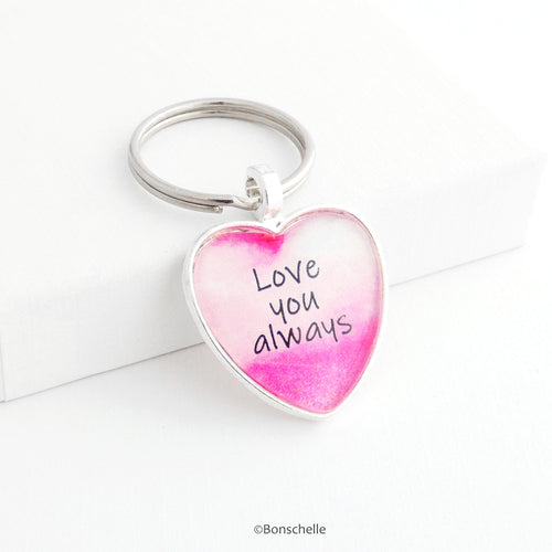 Silver toned heart shaped metal keyring with pink and white design and the worlds 'Love you Always' capped with a clear glass cabochon