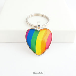 Heart shaped silver metal keyrings with a colourful bright rainbow stripe pattern capped with a clear glass cabochon.