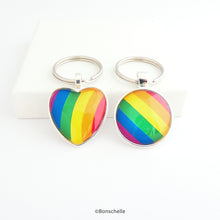 Load image into Gallery viewer, Heart shaped and round shaped silver metal keyrings with a colourful bright rainbow stripe pattern capped with a clear glass cabochon.
