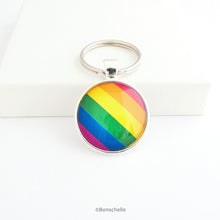 Load image into Gallery viewer, Round shaped silver metal keyrings with a colourful bright rainbow stripe pattern capped with a clear glass cabochon.