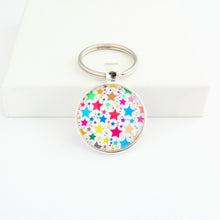 Load image into Gallery viewer, A round shaped silver toned metal keyring with a colourful star pattern design capped wtih a clear glass cabochon