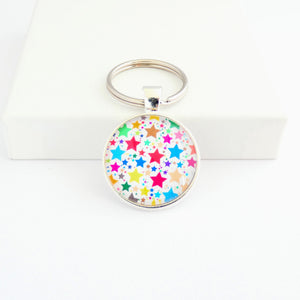 A round shaped silver toned metal keyring with a colourful star pattern design capped wtih a clear glass cabochon