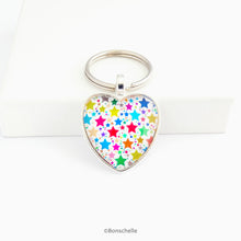 Load image into Gallery viewer, Heart shaped  silver toned keyring with a colourful star pattern