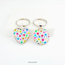 Load image into Gallery viewer, Heart shaped and a round shaped silver toned metal keyring with a colourful star pattern design capped wtih a clear glass cabochon.