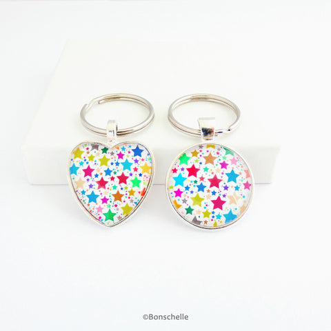 Heart shaped and a round shaped silver toned keyring with a colourful star pattern
