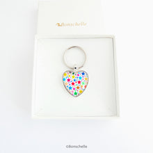 Load image into Gallery viewer, Heart shaped silver toned metal keyring with a colourful star pattern design capped wtih a clear glass cabochon. in a gfit box