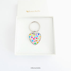 Heart shaped silver toned metal keyring with a colourful star pattern design capped wtih a clear glass cabochon. in a gfit box