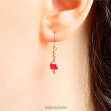 Load image into Gallery viewer, Drop earrings with a single bright red Swarovksi crystal beads, 3 smaller gold toned metal beads and 14K gold filled earwires shown being worn.
