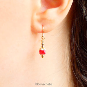 Drop earrings with a single bright red Swarovksi crystal beads, 3 smaller gold toned metal beads and 14K gold filled earwires shown being worn.