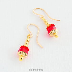Drop earrings with a single bright red Swarovksi crystal beads, 3 smaller gold toned metal beads and 14K gold filled earwires.