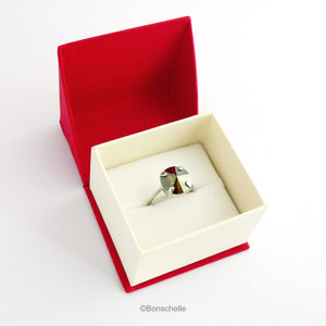 The silver toned solitaire ring for women with a deep bronze Swarovksi crystal stone shown in the jewellery box.