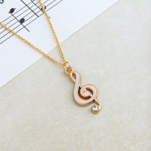 Pink enamel and gold treble clef shaped pendant with faux diamond and gold  necklace chain against backdrop of a music sheet
