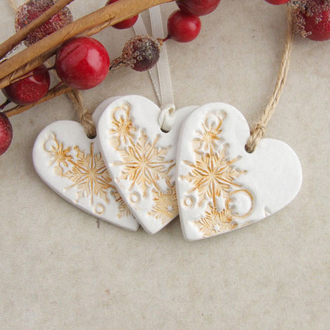 3 white clay heart shaped christmas decorations with golden snowflake accent