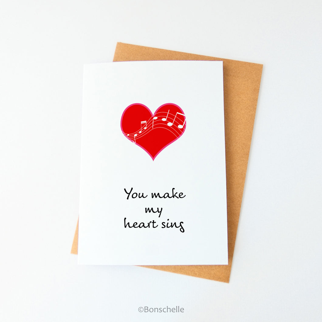 Front view of a handmade white greeting card with a red heart with white musical notes overlaid, and the words You Make My Heart Sing beneath, with a brown envelope.