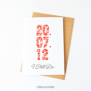 Front view of a handmade greeting Card with a personalised date in heart patterned numbers and the words 'I Still Do' beneath on the front, with a brown envelope.