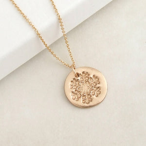 Small round polished bronze pendant with a snowflake texture and gold necklace chain