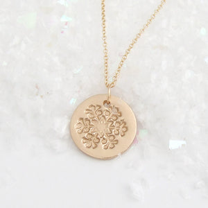 Small round polished bronze pendant with a snowflake texture and gold necklace chain against glittering snow
