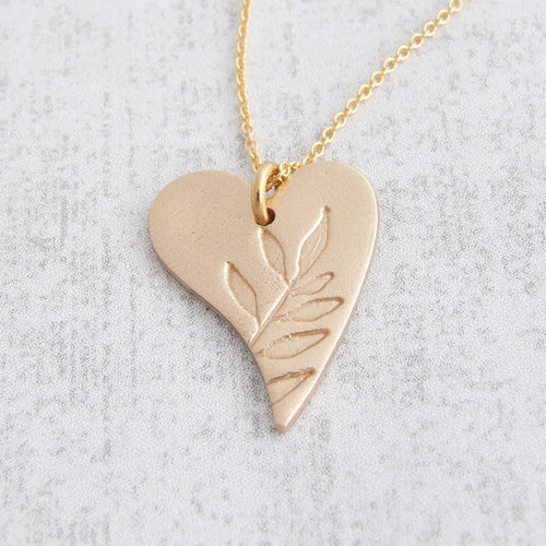 Gold bronze heart shaped pendant with leaf pattern on the front
