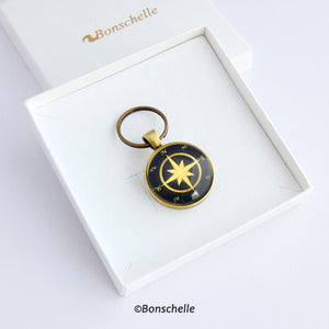 Front view of a personalised bronze metal round double sided keyring, with light bronze coloured compass rose on the front against a navy blue background  laying in a white gift box