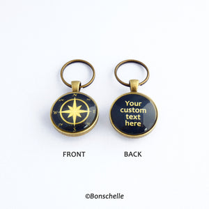 Front and back views of a personalised bronze metal round double sided keyring, with light bronze coloured compass rose on the front against a navy blue background, and the back wtih light bronze coloured text against a navy blue background.