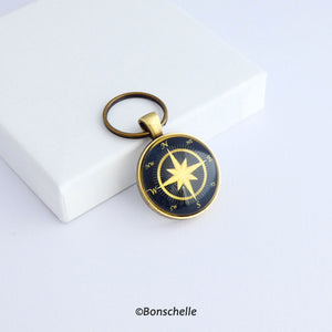 Front  view of a personalised bronze metal round double sided keyring, with light bronze coloured compass rose on the front against a navy blue background