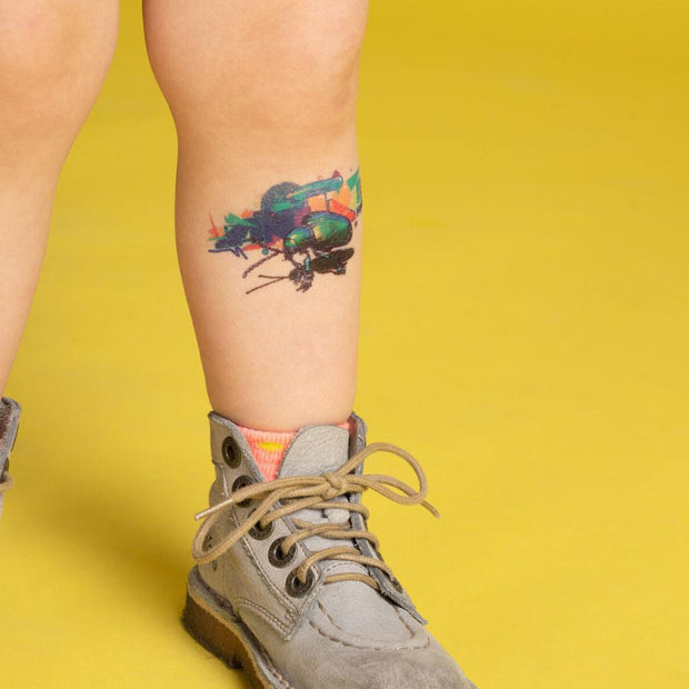 The leaf beetle temporary tattoo on a child's leg.