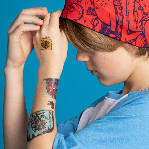 Teen boy with 3 of these robot temporary tattoos designed by professional artist, cartoonist Andre martel.