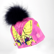 Left side view of the pink and purple butterflies beanie hat with navy fur pompom.
