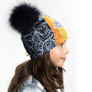 Left Side view of girl wearing Black and white doodle pattern toque with black pompon.