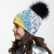 Side view of girl wearing Black and white doodle pattern toque with black pompon.