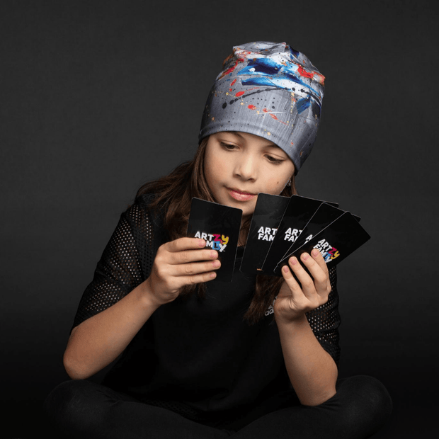 Girl wearing gray tuque with an abstract pattern with white, red, blue and yellow accents. Fit with everything!