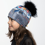 Side view of girl wearing gray, blue and white abstract pattern toque with black pompom.