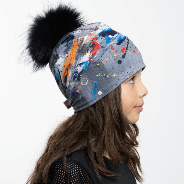 Left Side view of girl wearing abstract modern unisex toque with black pompon.