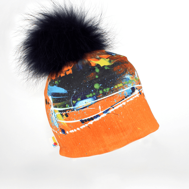 Right side view of the colourful orange beanie hat with navy blue pompom illustrated by Megane Fortin