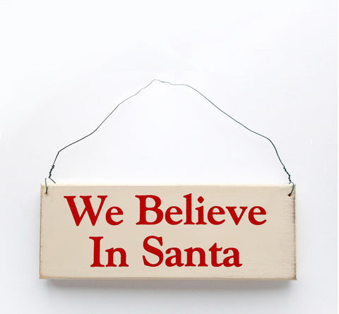 Wood sign saying: We Believe in Santa. Handmade from natural, ethically sourced wood in Pembroke, MA.