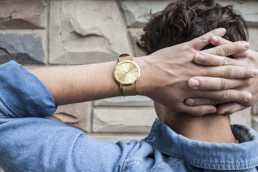 Unisex wristwatch with minimal gold dial serves as a sleek fashion accessory