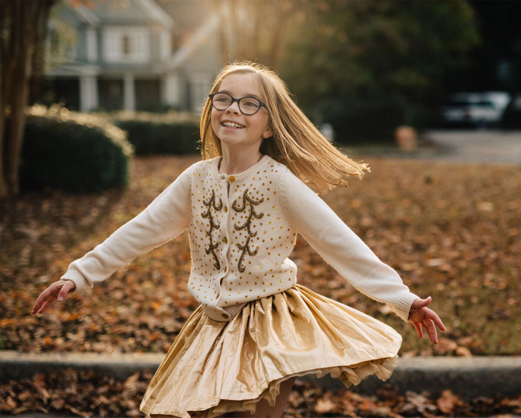 Little girl twirling in Pink Chicken white sweater and gold skirt