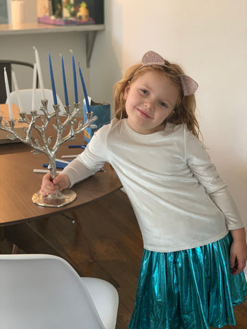 Julia stands next to her menorah, decorating for her favorite holiday!