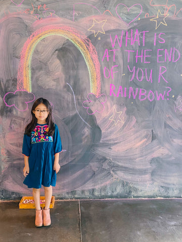 Luna wearing her Arianna Dress in front of a chalk board.
