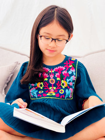 Luna reading in her Arianna Dress with bright embroidery.