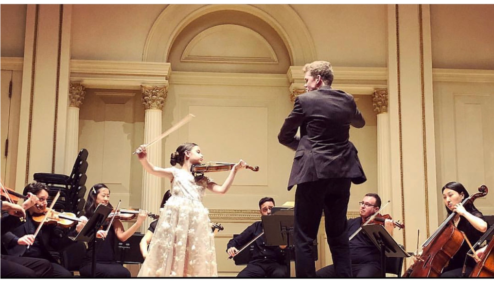 Pink Chicken customer performing at a violin concert in white dress