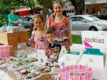 Girls stand behind a table with lots of cookies on it - all proceeds going to Cookies for Kids Cancer. Click to read about how we give back.