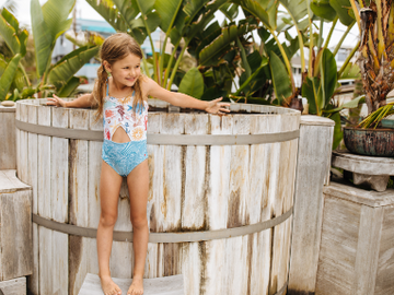 Little girl in her Carrie Cut out swimsuit stands by the hot tub. Click to view the full Swim Collection.