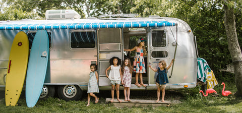 Girls wearing Pink Chicken in front of an airstream
